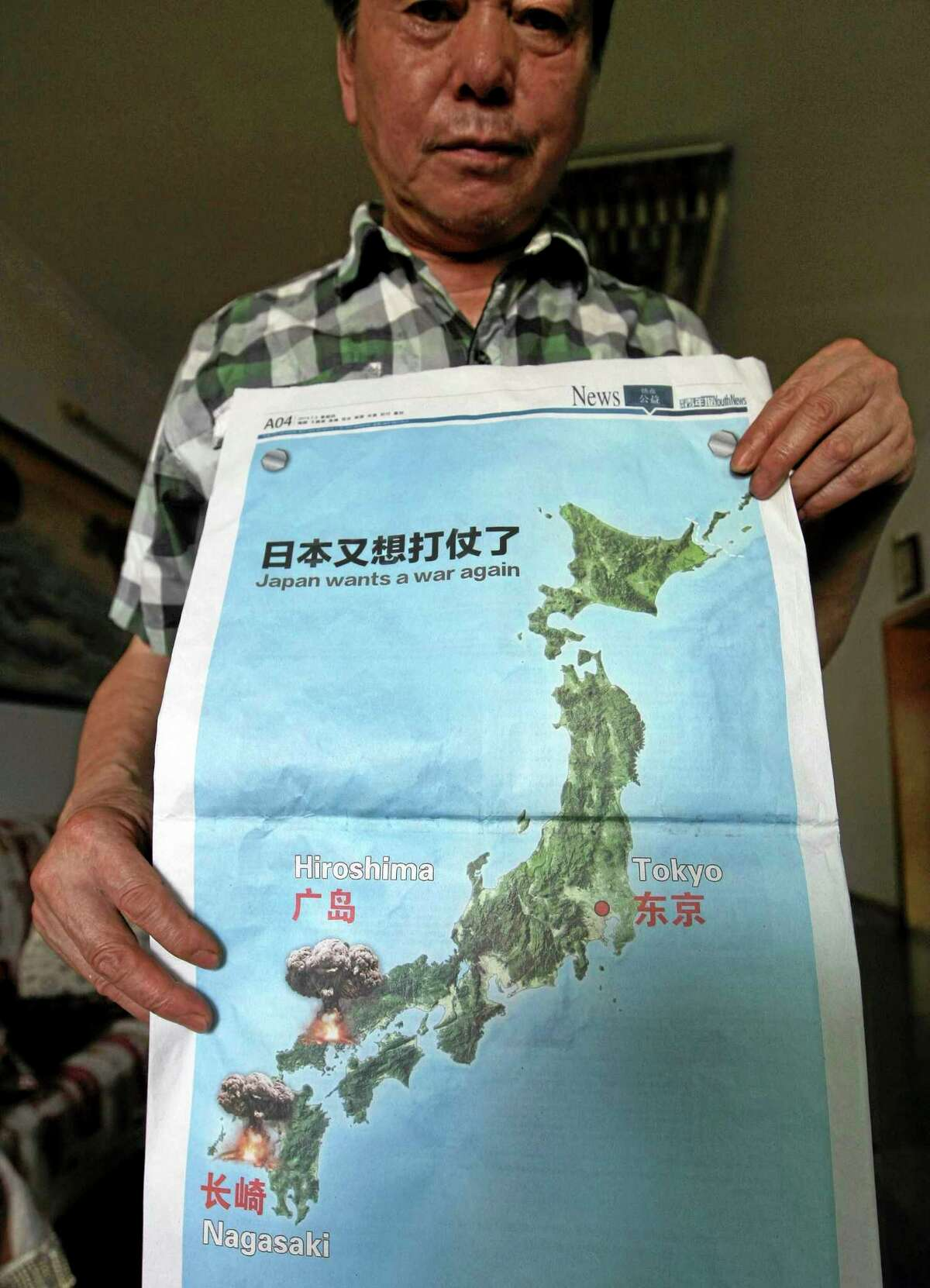 """A man poses with a full page advertisement with the headline """"Japan wants a war again"""" and showing mushroom clouds over Hiroshima and Nagasaki that was published on the July 3, 2014 issue of the Chonqging Youth Daily newspaper days after Japan's cabinet approved a reinterpretation of the country's pacifist postwar constitution in Chonqing in southwestern China on Wednesday July 9, 2014. (AP Photo) CHINA OUT"""