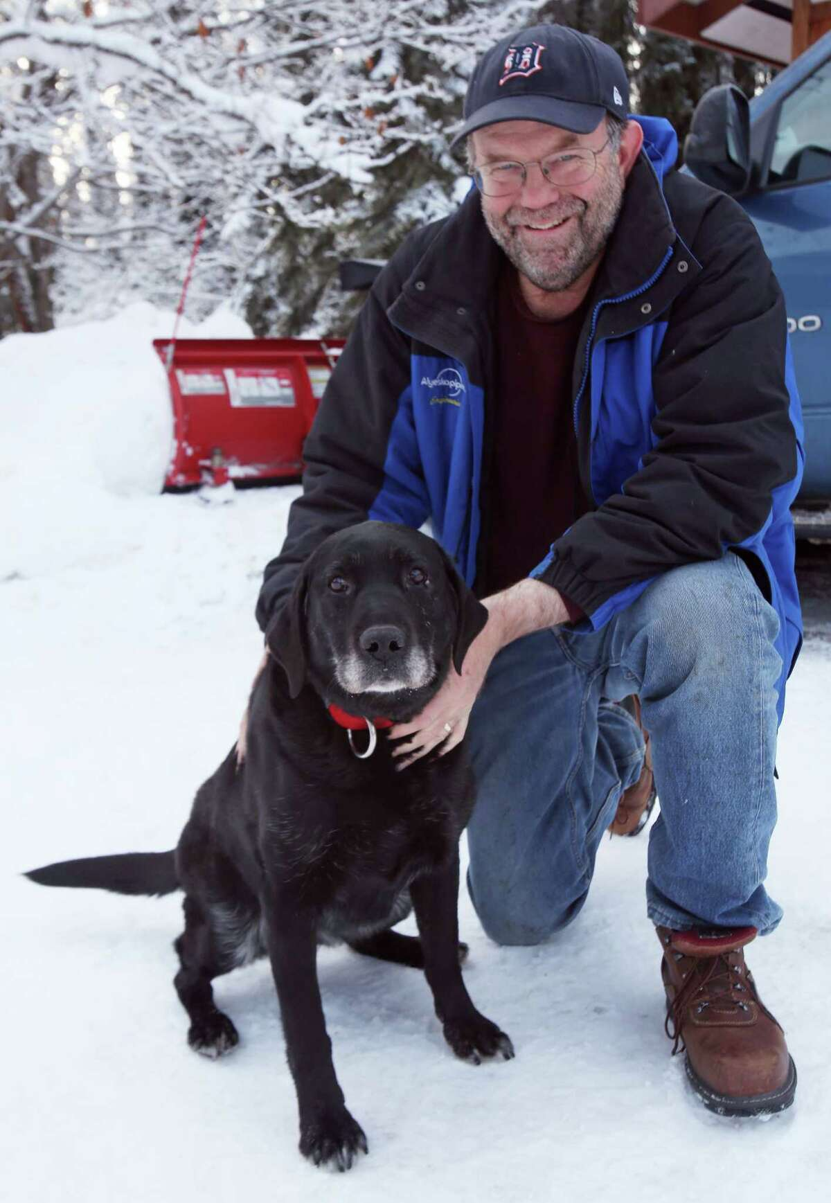 Ed Davis poses with his dog Madera at his home Thursday, Feb. 26, 2015, in Ester, Alaska. Madera, who is 11-years old and blind, survived two weeks in sub-zero temperatures after wandering away from home earlier this month. (AP Photo/The Fairbanks Daily News-Miner, Eric Engman)