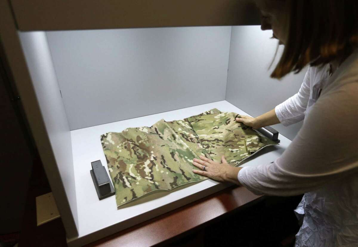 Clare King compares swatches of camouflage fabric in a shade box, at Propel LLC, a textile technology research company, in Pawtucket, R.I. The shade box is used to visually inspect camouflage designs and compare research fabrics to match a standard. King is president of Propel LLC.