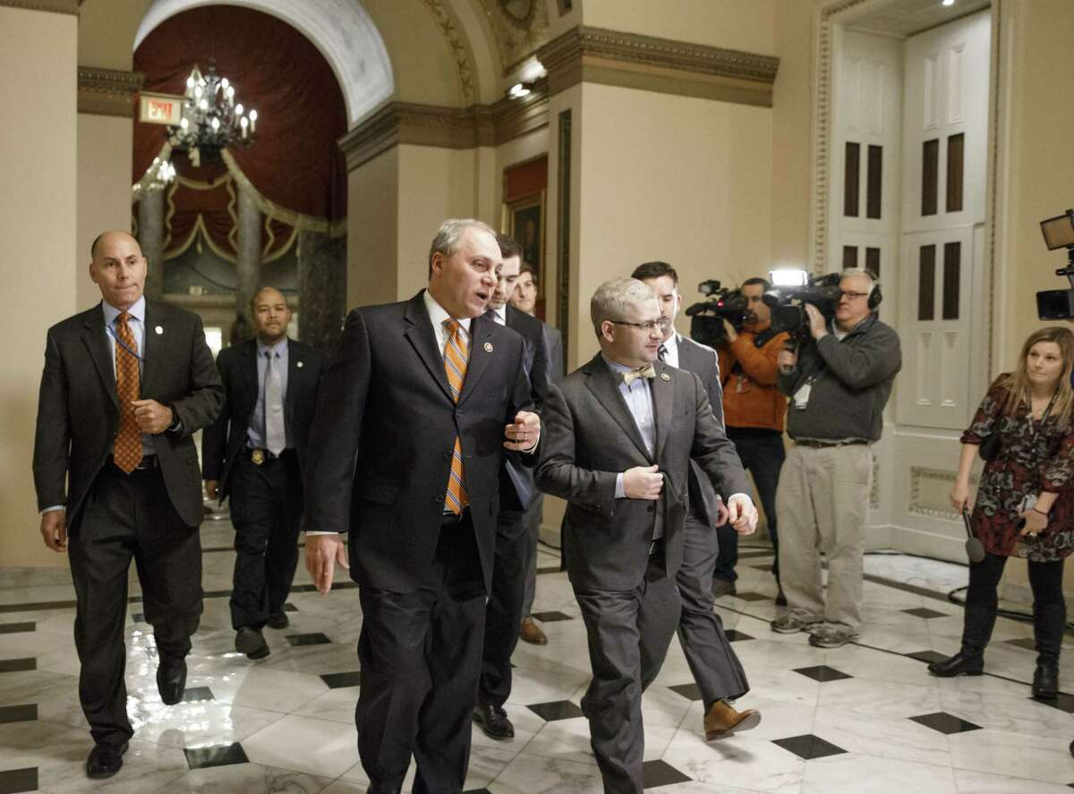House Majority Whip Steve Scalise, R-La., center left, and Rep. Patrick T. McHenry, R-N.C., the chief deputy whip, walk to the chamber as Congress passed a one-week bill late Friday night, Feb. 27, 2015, to avert a partial shutdown of the Homeland Security Department, as leaders in both political parties quelled a revolt by House conservatives furious that the measure left President Barack Obama's immigration policy intact, at the Capitol in Washington.