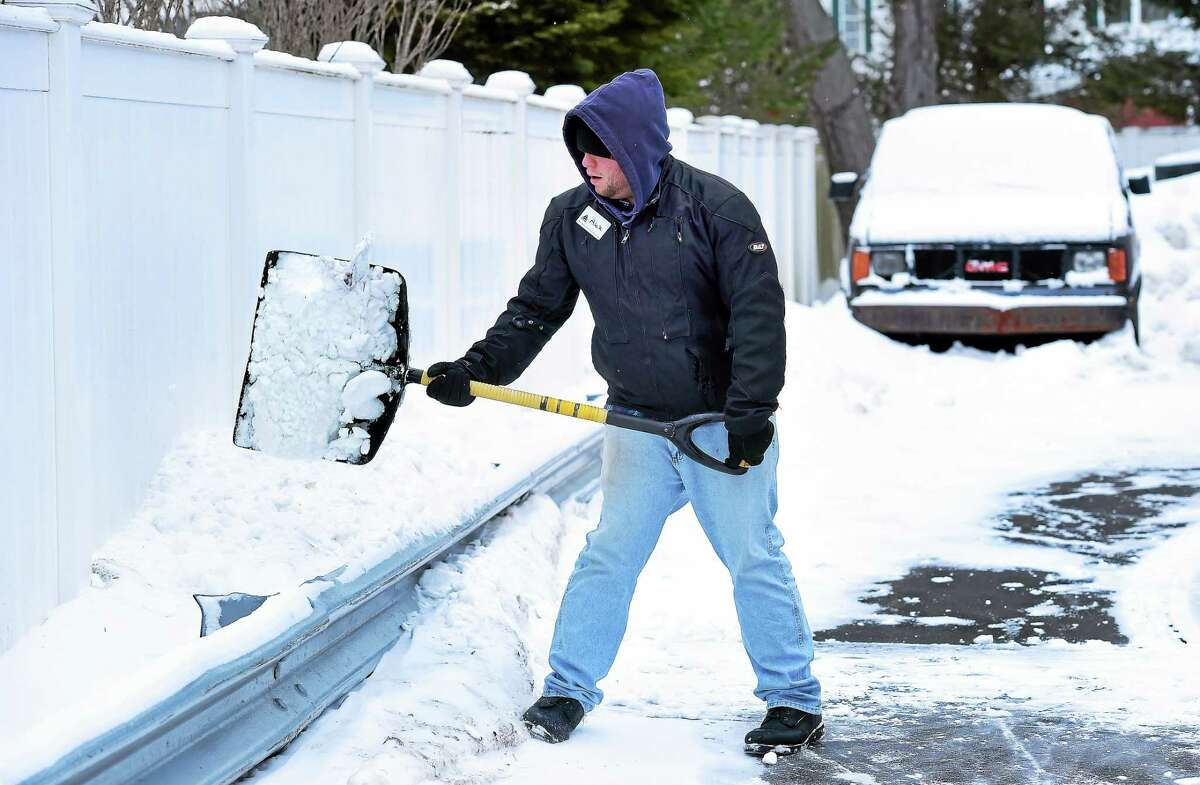 Alex Butler clears the snow at Post Parkway Service in Milford on Sunday morning 2/15/2015.