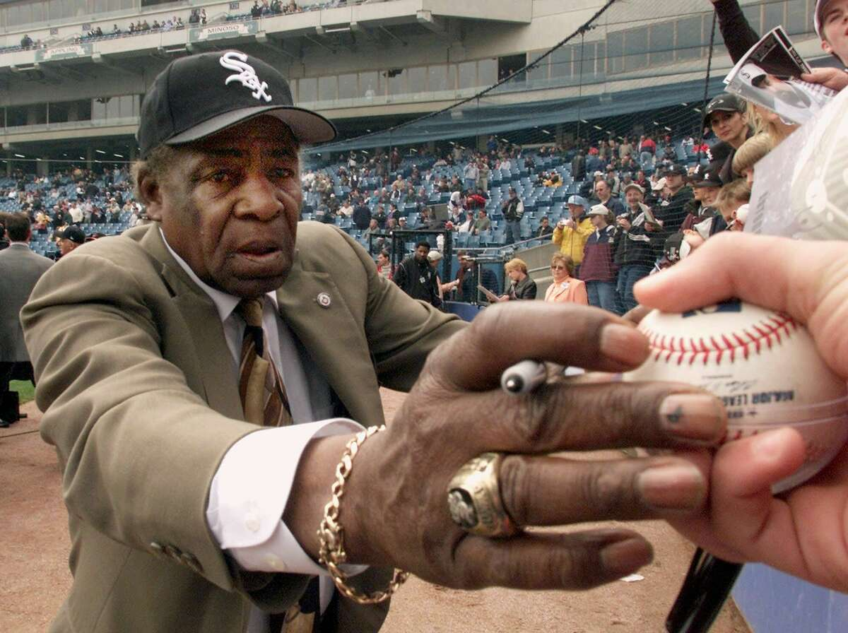 """In a April 6, 2001 photo, Chicago White Sox legend Orestes """"Minnie"""" Minoso signs autographs prior to the Sox' home opener against the Detroit Tigers, at Comiskey Park in Chicago."""