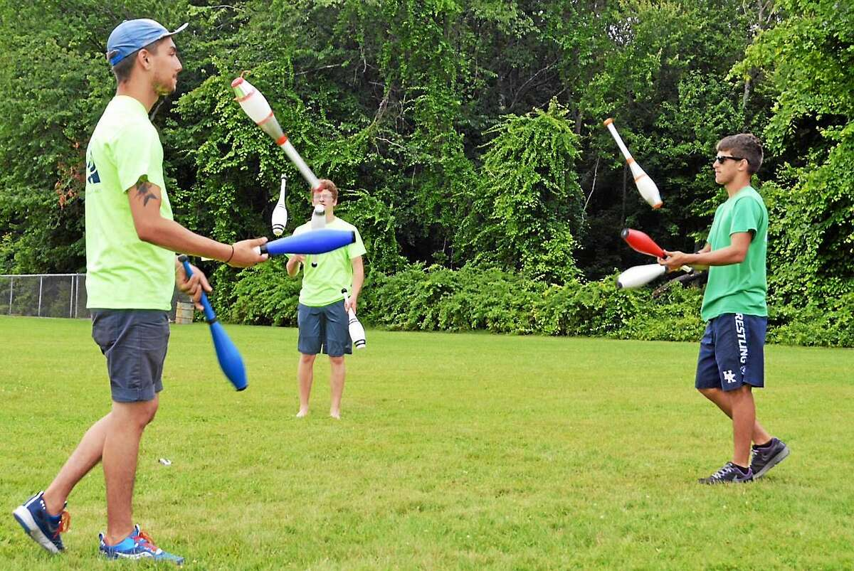 Counselors, from left, Evan Knoll, Shane Keegan and Nick Adler demonstrate juggling with clubs during a break at the Children's Circus of Middletown camp.