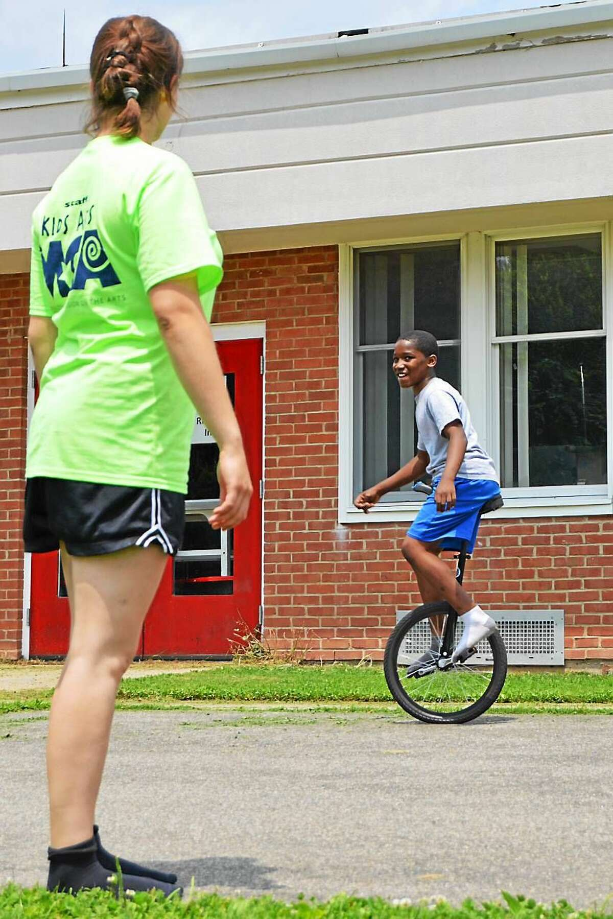 Counselor Carolyn Reid, 16, of Middletown, watches spots camper Tavon Outlaw, 10, of Middletown, on the unicycle. Outlaw has been attending the Children's Circus of Middletown for three years and his favorite skills are stilting and unicycling.