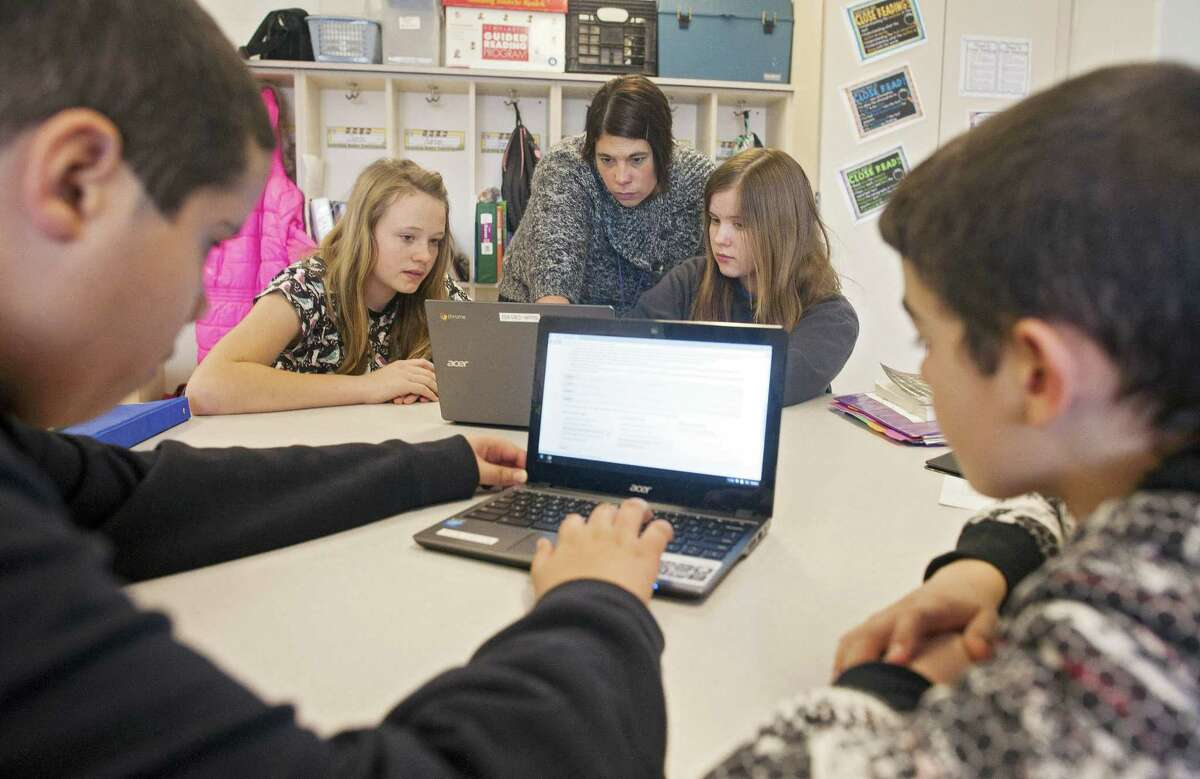 Sixth-grade teacher Carrie Young, back center, answers questions from her students about an exercise on their laptops as they practice for the the Common Core State Standards Test in her classroom at Morgan Elementary School South in Stockport, Ohio.