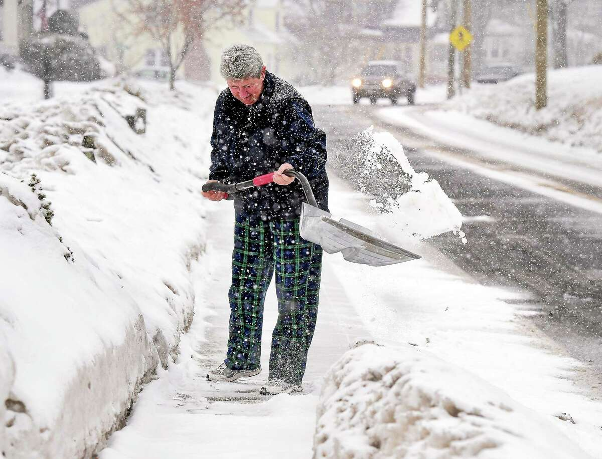 Sheryl Thompson shovels snow from the sidewalk in front of her house on Seaside Ave. in Milford Sunday afternoon as March came in like a lion for cold-weary local residents.