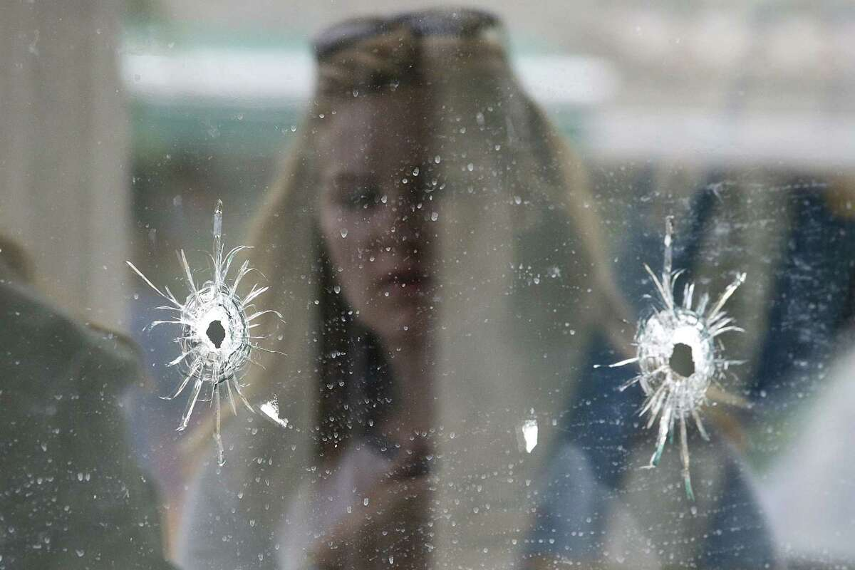 In this May 24, 2014 photo, a woman looks at the bullet holes on the window of IV Deli Mark where a mass shooting took place near the University of California, Santa Barbara campus, in the Isla Vista beach community. More than 900 laws approved by the Legislature and signed by the governor will take effect Jan. 1, 2015.