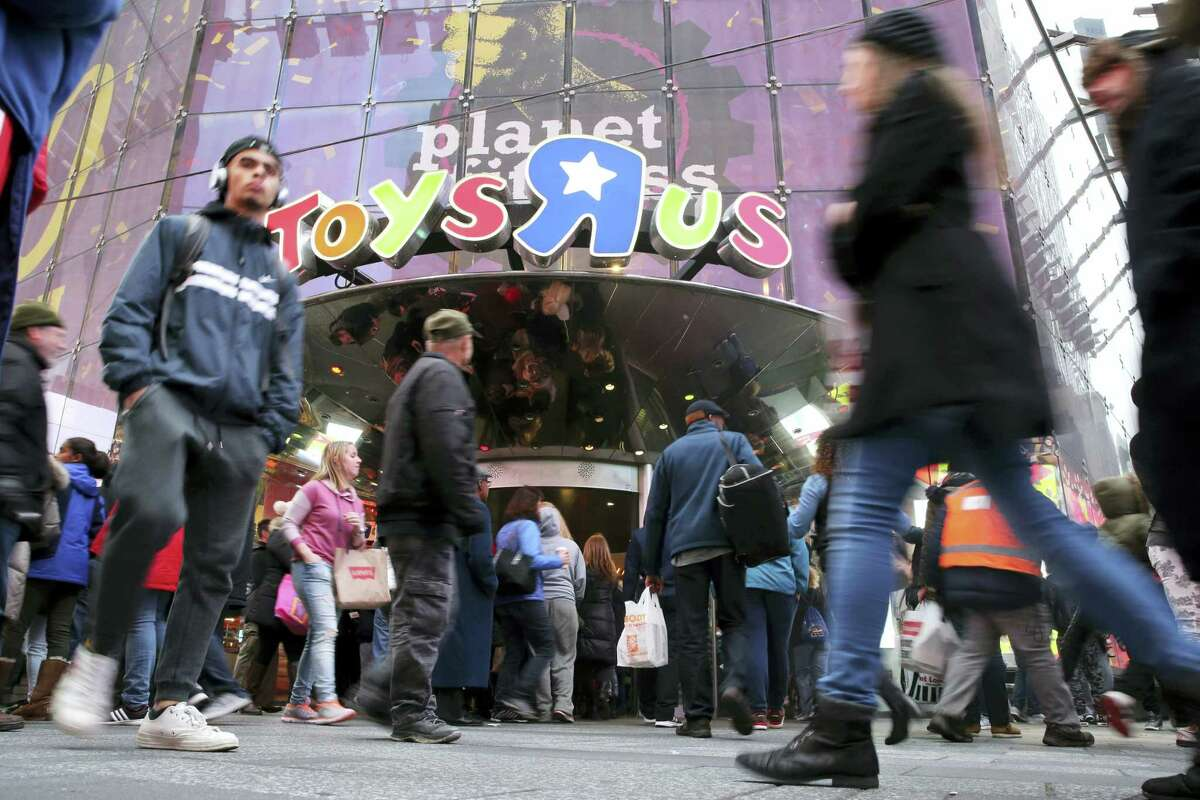 Visitors to New York's Times Square walk past the Toys R Us store, Wednesday, Dec. 30, 2015. Fourteen years after it began wowing millions of tourists with its indoor 60-foot Ferris wheel and a growling 20-foot Tyrannosaurus, the giant Toys R Us flagship store in Times Square closes its doors Wednesday.