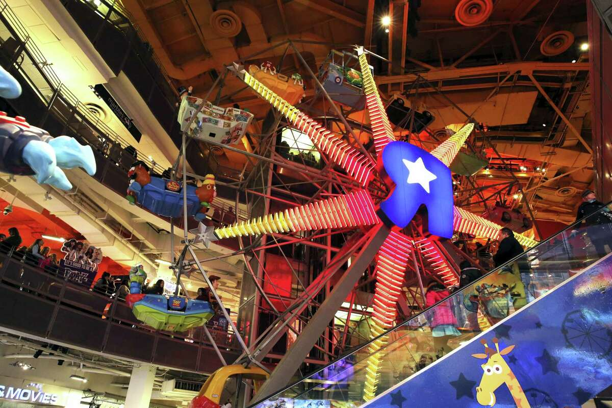 The Ferris Wheel at the Toys R Us store in New York's Times Square is seen, Wednesday, Dec. 30, 2015. Fourteen years after it began wowing millions of tourists with its indoor 60-foot Ferris wheel and a growling 20-foot Tyrannosaurus, the giant Toys R Us flagship store in Times Square closes its doors Wednesday.