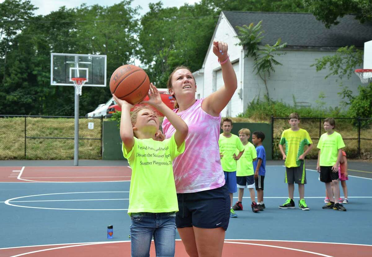 """Summer Quest Camp counselor Lindsey Dionne gives pointers to Aravella Alexander, 9, during a """"Make-It-Take-It"""" game shortly after the opening of The Village District Basketball Courts Wednesday morning in Portland. Summer Quest campers sponsored by the Portland Park & Rec attended the opening. Dionne and her teammates at Portland High School won the CIAC Class S Basketball Championship in 2011."""