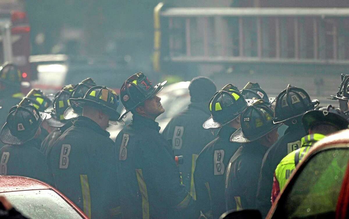 Firefighter look on at the scene of a multi-alarm fire at a four-story brownstone in the Back Bay neighborhood near the Charles River, Wednesday, March 26, 2014, in Boston. (AP Photo/Steven Senne)