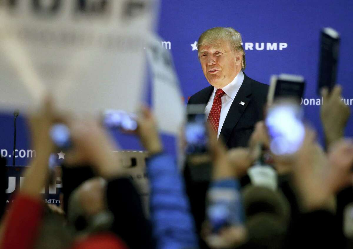 Republican presidential candidate Donald Trump is greeted by an audience holding placards and mobile phones at the start of a campaign event Monday, Dec. 28, 2015, in Nashua, N.H. (AP Photo/Steven Senne)