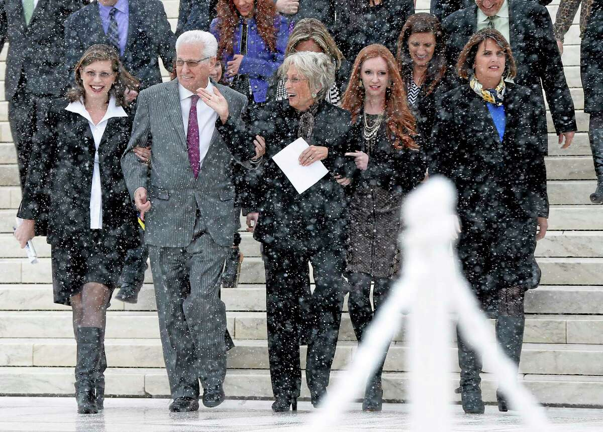 David Green, founder and chief executive officer of Hobby Lobby, second from left, walks with his wife Barbara, center, and members of their family as they acknowledge a cheer from demonstrators in the crowd as they descend the steps of the Supreme Court in Washington, Tuesday, March 25, 2014, after the court heard oral arguments in the challenges of President Barack Obama's health care law requirement that businesses provide their female employees with health insurance that includes access to contraceptives. Supreme Court justices are weighing whether corporations have religious rights that exempt them from part of the new health care law that requires coverage of birth control for employees at no extra charge. (AP Photo/Charles Dharapak)