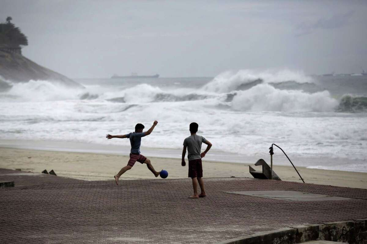 FILE - In this June 20, 2014 file photo, boys play football as waves break on Sao Conrado beach in Rio de Janeiro, Brazil. World Surf League spokesman Dave Prodan said in an emailed statement Wednesday, April 29, 2015, that Sao Conrado beach had to be removed from its venue list ìdue to pollution issues.î The beach had been a backup for the May 11-22 Rio Pro event, to be used in case of sub-par waves or other issues at the primary venue, nearby Barra da Tijuca beach. (AP Photo/Matt Dunham, File)