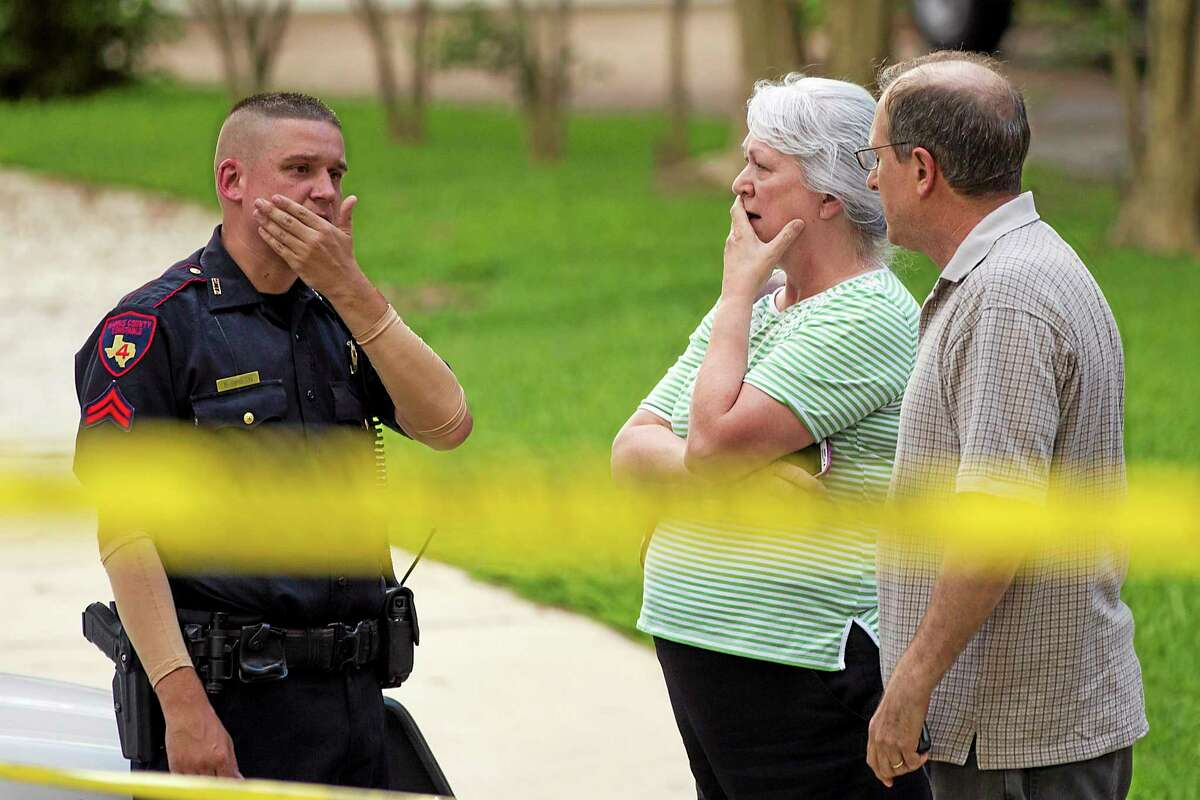 People stand with a law enforcement officer near the scene of a shooting Wednesday, July 9, 2014, in Spring, Texas.