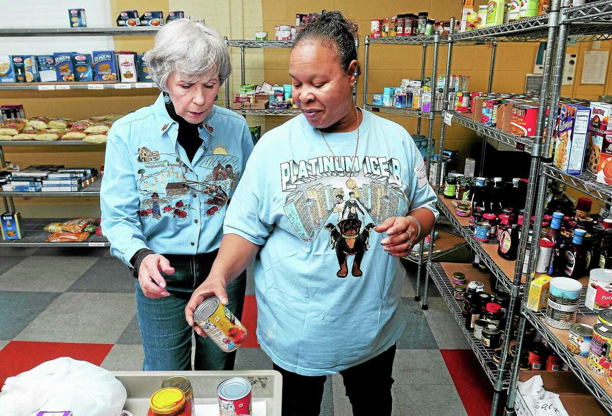 In this 2013 archive photo, a volunteer helps a client gather food at the St. Vincent De Paul Place Amazing Grace Food Pantry in Middletown.