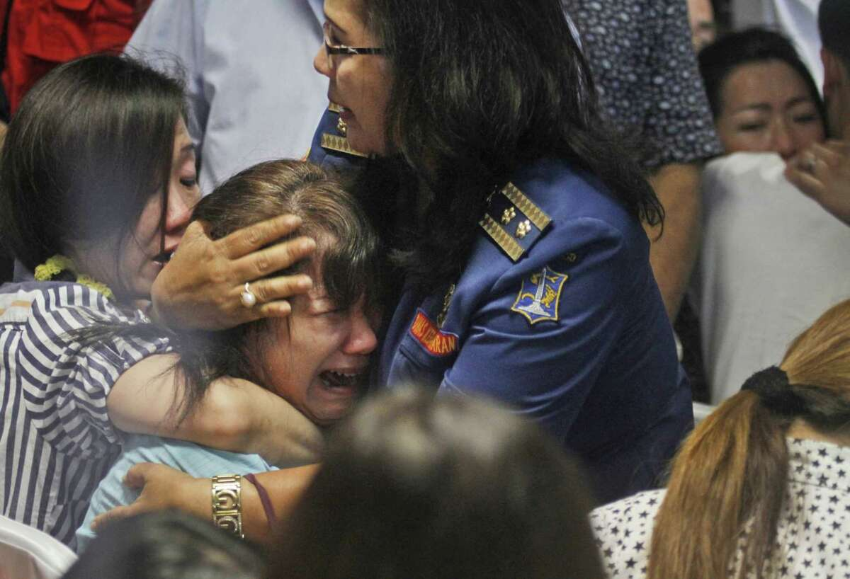 Relatives of passengers of the missing AirAsia Flight 8501 react upon seeing the news on television about the findings of bodies on the waters near the site where the jetliner disappeared, at the crisis center at Juanda International Airport in Surabaya, East Java, Indonesia on Dec. 30, 2014.