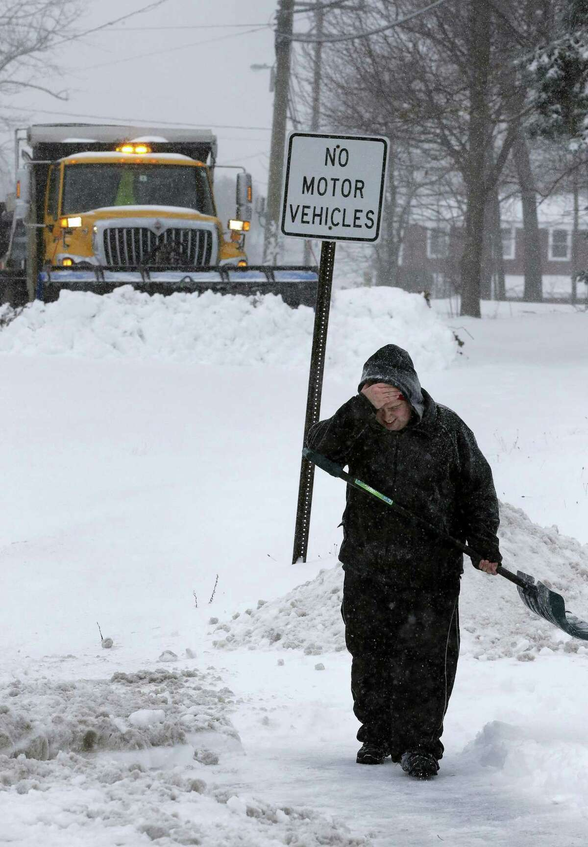 Corey Nachman, of Portsmouth, N.H., holds his hand to his face while shoveling his driveway, Tuesday in Portsmouth.