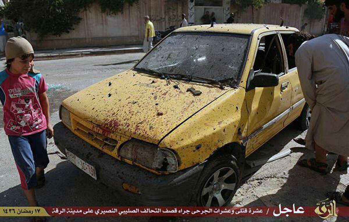 """This July, 4, 2015 photo provided by a website of the Islamic State group, shows people inspecting a car purportedly damaged by U.S.-led airstrikes on Raqqa, Syria. A series of U.S.-led coalition airstrikes targeting the Islamic State group's stronghold of Raqqa in eastern Syria has killed at least 10 militants and wounded many others. The airstrikes were confirmed by the coalition, Raqqa-base activists and the Islamic State group. Arabic on banner reads, """"Raqqa Urgent / Ten killed and tens wounded by crusader (Christian)-Nusayri (Alawite) coalition on Raqqa city. 17 Ramadan 1436 Hijri."""""""