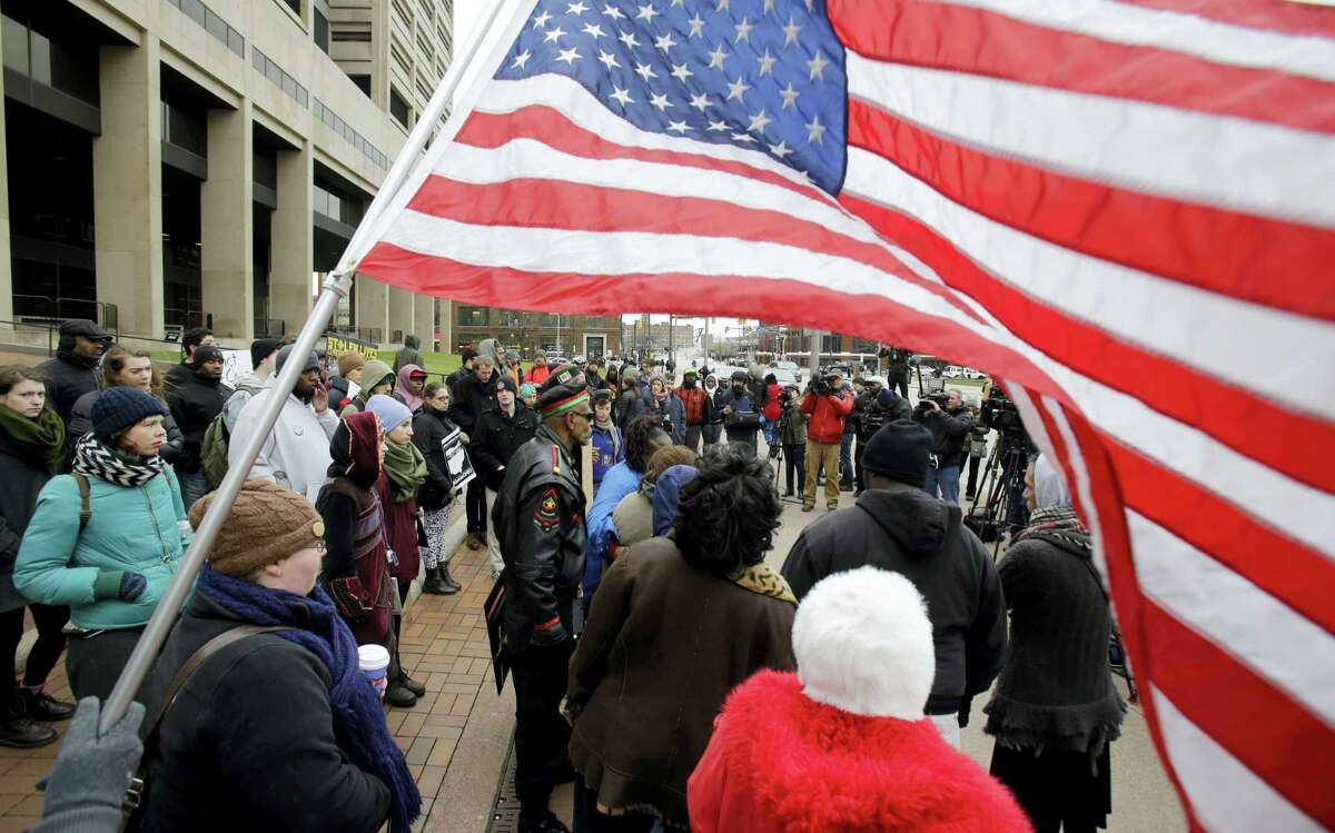 People protest outside the Cuyahoga County Justice Center, Tuesday, Dec. 29, 2015, in Cleveland. People marched peacefully in front of the Justice Center in downtown Cleveland to protest a grand jury's decision not to indict two white Cleveland police officers in the fatal shooting of Tamir Rice, a black 12-year-old boy who was playing with a pellet gun.