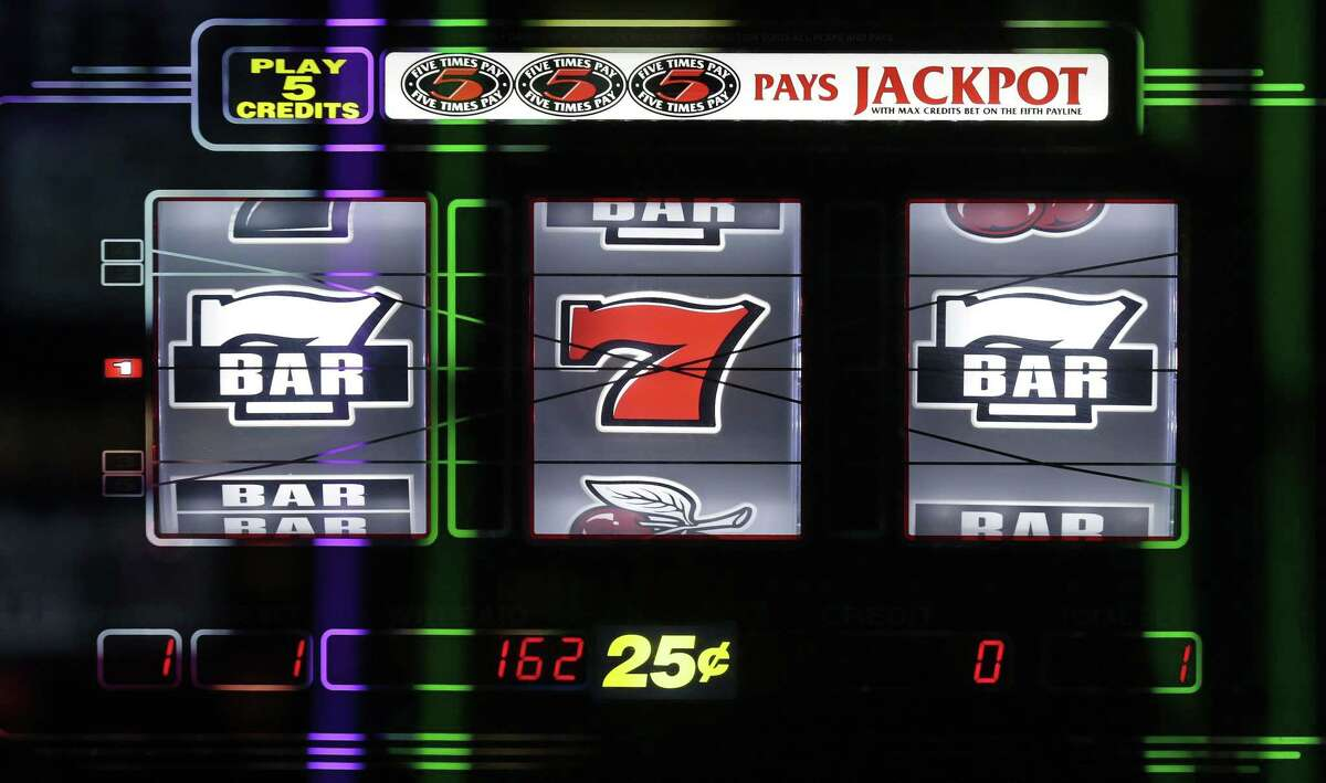 The display of a slot machine glows on the floor of the Plainridge Park Casino in Plainville, Mass. on June 23, 2015. The Plainridge Park Casino represents the first gambling destination to open since state lawmakers approved a casino law in 2011.