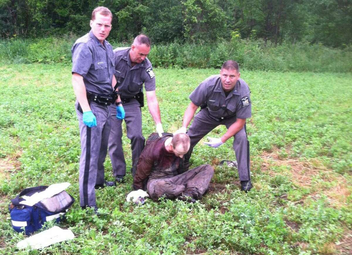 Police stand over David Sweat after he was shot and captured near the Canadian border Sunday, June 28, 2015, in Constable, N.Y. His capture came two days after his escape partner, Richard Matt, was shot and killed by authorities.