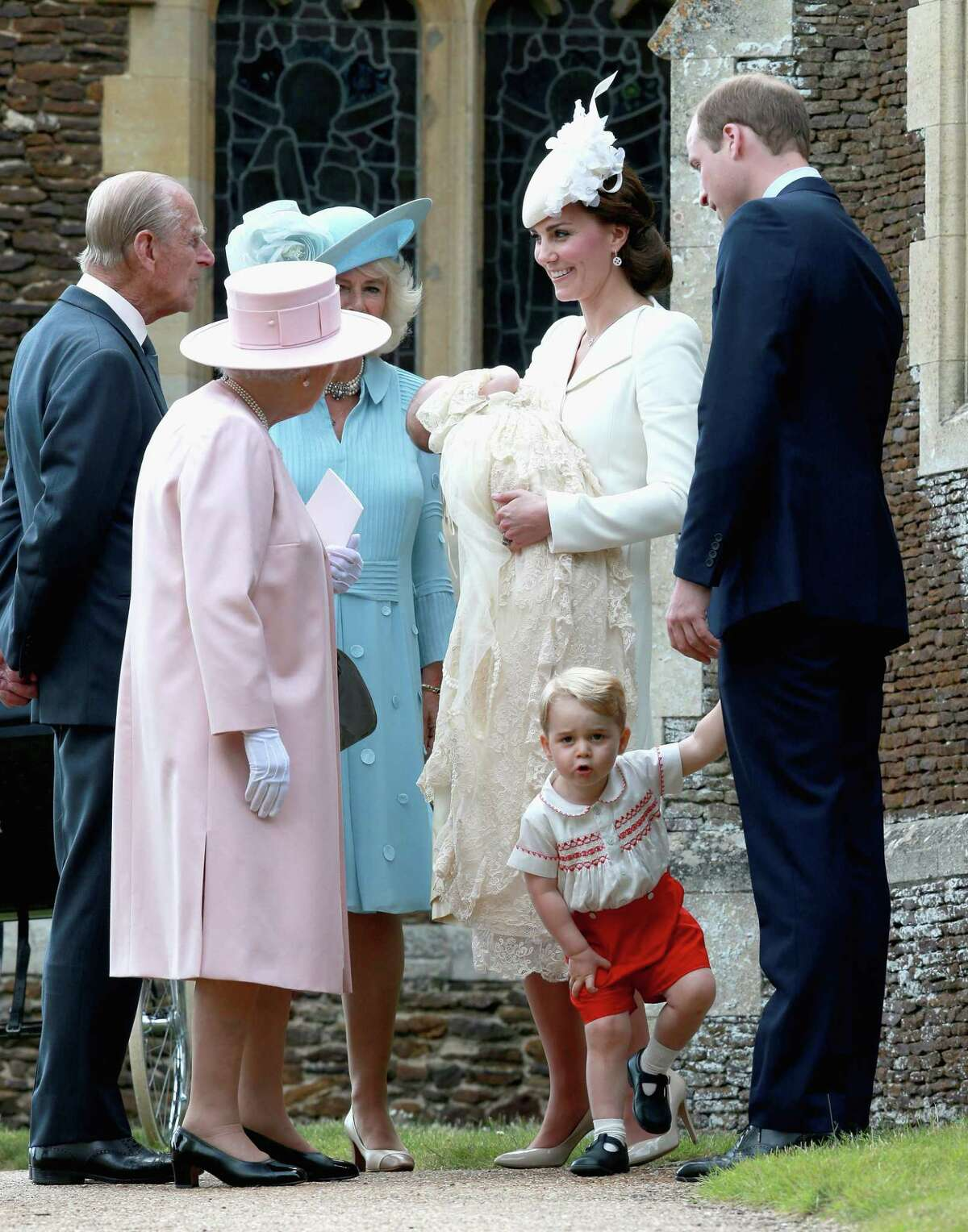 Kate, the Duchess of Cambridge, centre right, holding their daughter Princess Charlotte of Cambridge stands next to Britain's Prince William, Duke of Cambridge, holding their son Prince George of Cambridge's hand, as they talk to Britain's Queen Elizabeth II, left, and Prince Phillip and Camilla, Duchess of Cornwall, after the Christening of Princess Charlotte of Cambridge at St. Mary Magdalene Church in Sandringham, England on Sunday, July 5, 2015.