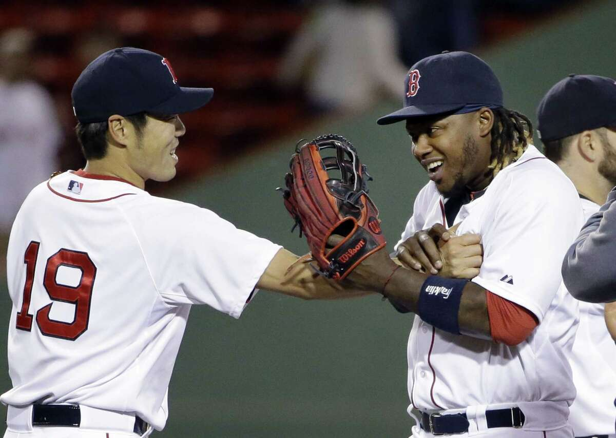 Boston Red Sox closer Koji Uehara (19) grabs Hanley Ramirez to celebrate after they defeated the Toronto Blue Jays 4-1 in a baseball game at Fenway Park in Boston, Wednesday, April 29, 2015. (AP Photo/Elise Amendola)