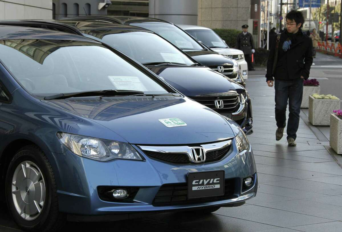 In this Jan. 30, 2010 file photo, a man looks at Honda Motor Co.'s Civic hybrid cars in front of the Japanese automaker's headquarters in Tokyo. Slow sales and falling gasoline prices have prompted Honda to stop selling gas-electric hybrid and natural gas-powered versions of its Civic compact car, the automaker said on June 15, 2015.