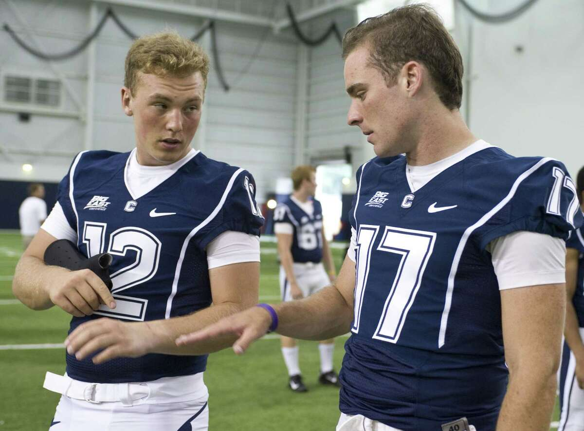 Former UConn quarterback Casey Cochran, left, takes a brace off to show his injury to fellow quarterback Blaise Driscoll, right, during an NCAA football media day in Storrs, Conn. on Aug. 10, 2012.