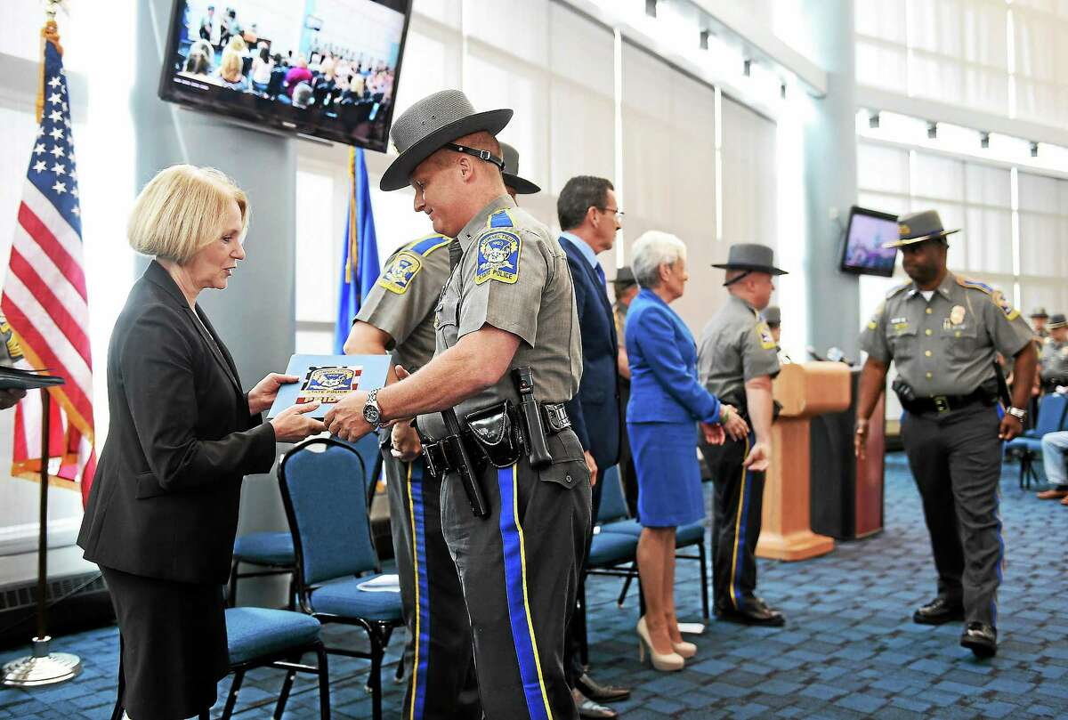 State police Lt. Michael Hofbauer receives a citation Tuesday from Commissioner Dora B. Schriro during a ceremony for troopers, local police, federal officers and civilians involved in the reponse to the Sandy Hook Elemtary School shootings in December 2012. Hofbauer received his citation as a first responder to the shootings. The awards were held at Rentschler Field in East Hartford.