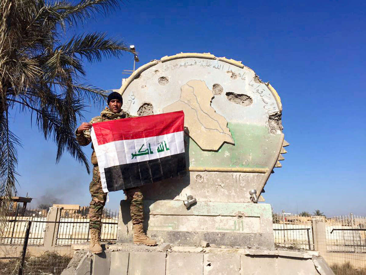 An Iraqi soldier holds a national flag in the government complex in central Ramadi Monday.