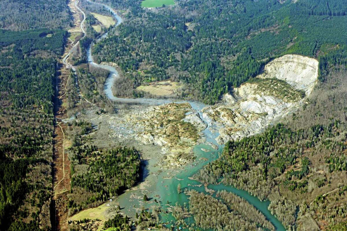 This aerial photo taken Monday, March 24, 2014 shows the massive mudslide that killed at least eight people Saturday and left dozens missing, near Arlington, Wash. The search for survivors grew Monday, raising fears that the death toll could climb far beyond the eight confirmed fatalities. (AP Photo/Ted S. Warren)