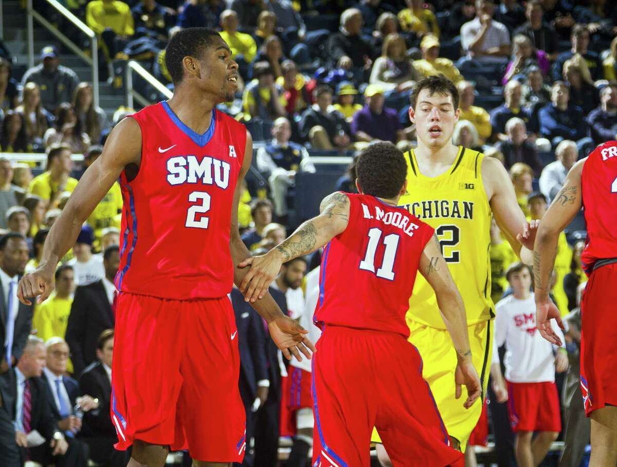 SMU center Yanick Moreira (2) and guard Nic Moore (11) celebrate after a basket during a recent game.