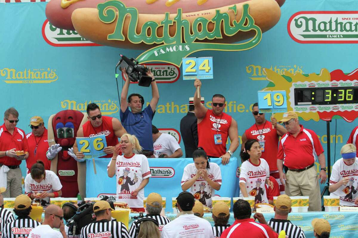 """Competitors, including Miki Sudo, second from left, and Sonya """"Black Widow"""" Thomas, center, take part in Nathan's Famous Fourth of July International Hot Dog Eating Contest women's competition Saturday July 4, 2015 in the Coney Island section in the Brooklyn borough of New York. Sudo won the competition eating 38 hot dogs and buns in 10 minutes. Thomas came in second eating 31 hot dogs and buns in 10 minutes. (AP Photo/Tina Fineberg)"""