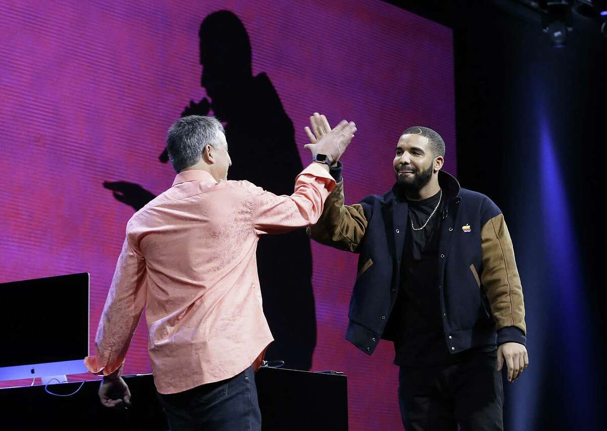 Musician Drake, right, high-fives Eddy Cue, Apple senior vice president of Internet Software and Services, during the Apple Worldwide Developers Conference in San Francisco June 8.