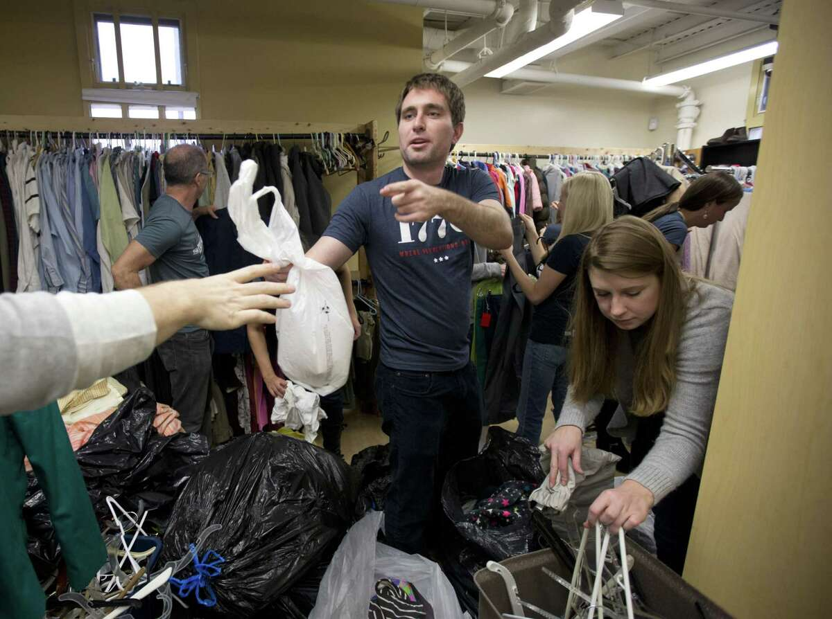 """This Dec. 16, 2014 photo shows Patrick McAnaney, center, and Morgan Gress, right, from the company 1776, as they volunteer in the clothing room at Bread for the City with a group of their coworkers in Washington. Those under 30 today are more likely to say that citizens have a """"very important obligation"""" to give their time, an Associated Press-GfK poll finds."""