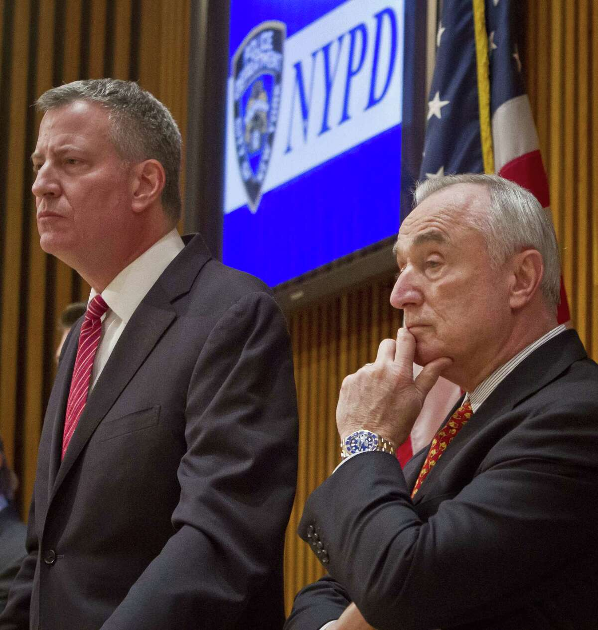 Mayor Bill de Blasio, left, and NYPD Commissioner Bill Bratton, right, listen during a press conference after attending a promotion ceremony for police officers on Dec. 19, 2014 in New York.