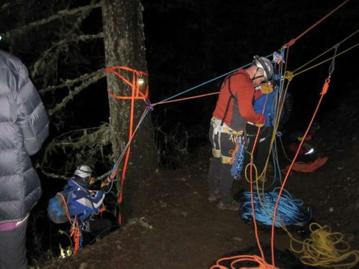 This Dec. 25 photo provided by Emily Amsler via the Oregon Humane Society shows John Thoeni, left, an Oregon Humane Society volunteer beginning his descent to save Sandy, a yellow Labrador who got spooked on a Christmas Day hike in the Columbia Gorge.