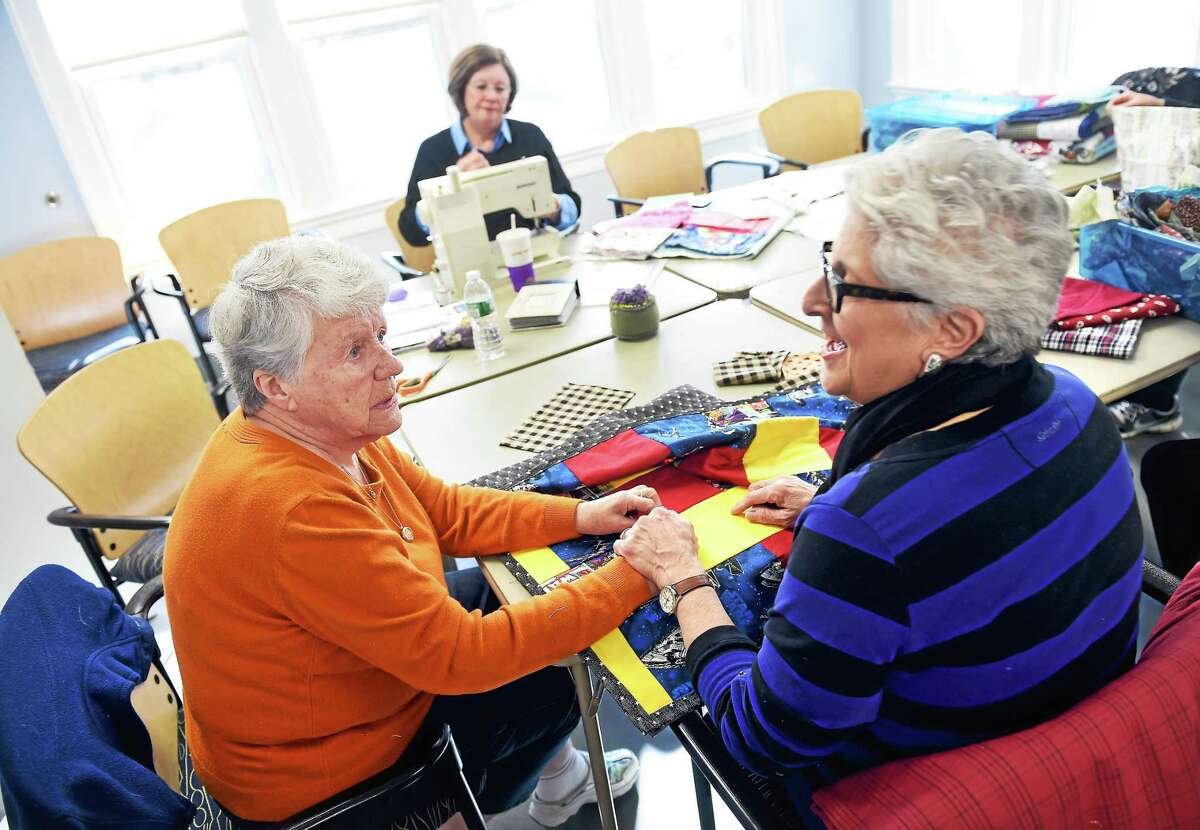 Barbara Zygmunt, left, of Madison looks over a lap quilt with Rachel McNellis of Westbrook, right, at the Madison Senior Center. The quilts made by Quilts of Joy are donated to the New Horizons Violence Services in Middletown. Pictured below is a lap quilt.