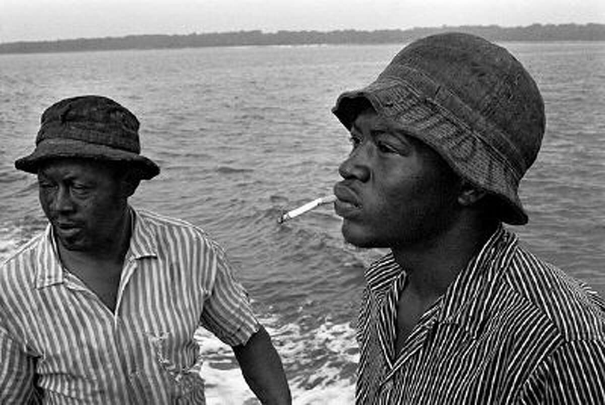 """This handout photo provided by Jeanne Moutoussamy-Ashe titled """"A shrimper and his son"""" is part of photographs donated by Jeanne Moutoussamy-Ashe to the African-American history museum at the Smithsonian. Bank of America officials tell The Associated Press they will give the museum 61 photographs by Moutoussamy-Ashe, the wife of the late tennis player Arthur Ashe. She documented Daufuskie Island between 1977 and 1981 and the Gullah/Geechee people who lived there. (AP Photo/Jeanne Moutoussamy-Ashe, Smithsonian)"""