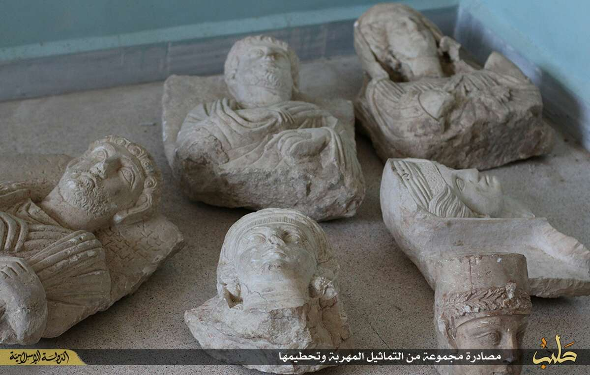 """This image posted on a militant website by the Aleppo branch of the Islamic State group on Friday, July 3, 2015, which has been verified and is consistent with other AP reporting, shows items that the group claims are six smuggled archaeological pieces from the historic central town of Palmyra. An IS statement says the busts were found when the smuggler was stopped at a checkpoint and was later referred to an Islamic which ordered that they be destroyed and the man be whipped. Arabic on the caption reads, ìa collection of smuggled statues was destroyed."""" (militant website via AP)"""