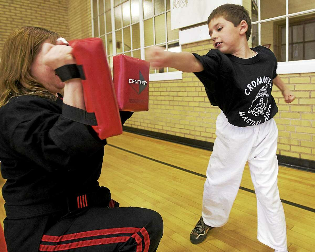 Devin Rigano, 7, of Middletown practices his punching with an instructor at Cromwell Martial Arts in Middletown in this 2010 file photo.