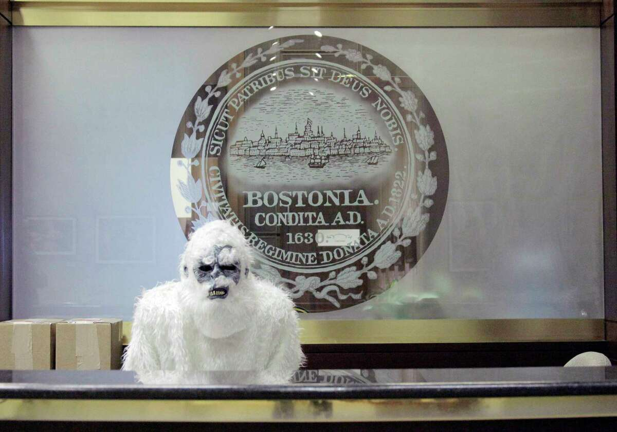 In this March 6 file photo, provided by Eric Gulliver, an anonymous creature known as The Boston Yeti poses in front of the Boston logo at City Hall in Boston. Smiles were in short supply as a series of blizzards dumped 9 feet of snow on Boston. Enter a mysterious do-gooder in an abominable snowman costume, who ran around mugging for cameras, dug out stranded drivers, gained folk hero status among winter-weary Bostonians.