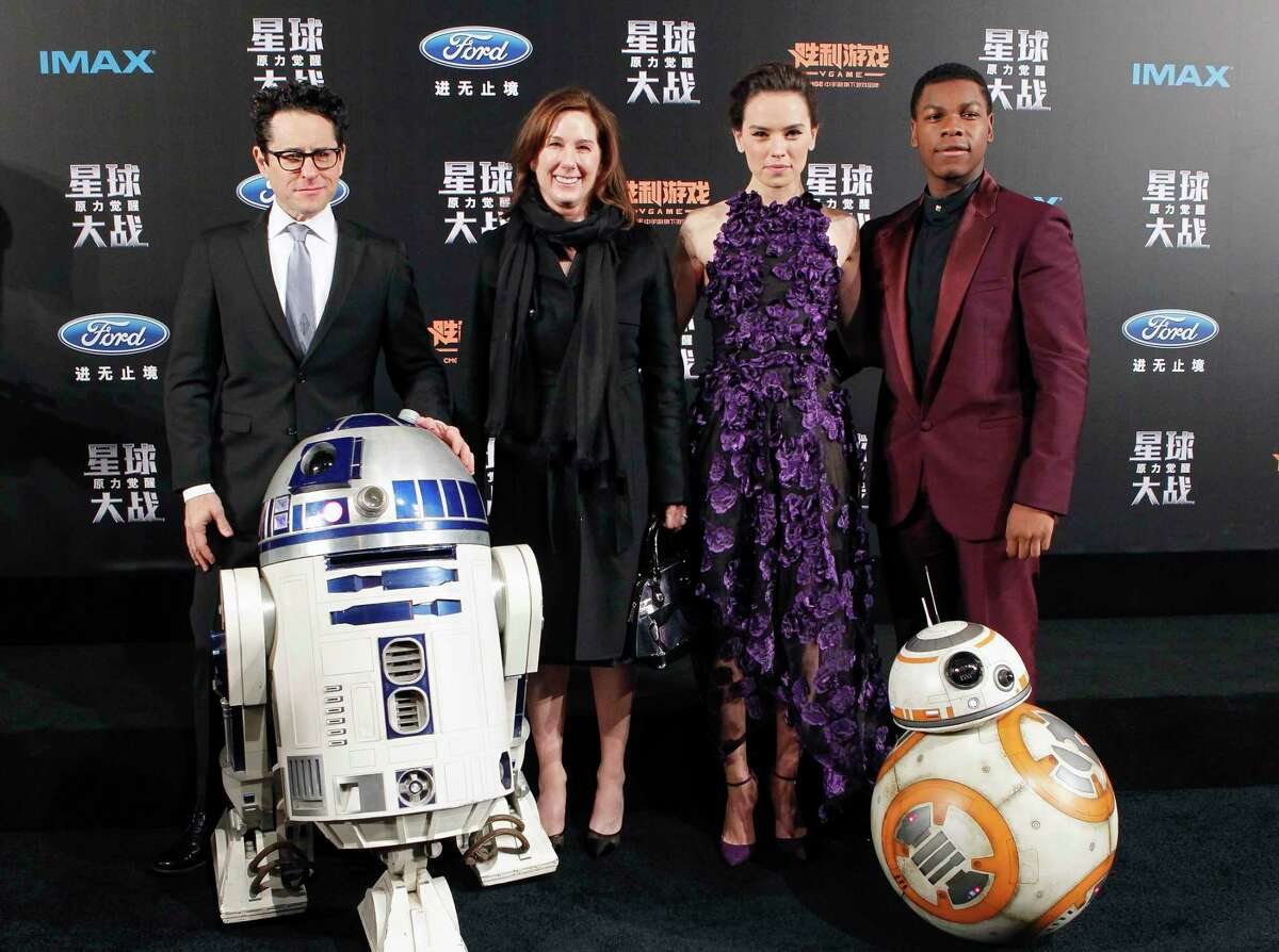 """From left, director J.J. Abrams, producer Kathleen Kennedy, actress Daisy Ridley and actor John Boyega pose with droids character BB-8 and R2-D2 on stage during the premiere of """"Star Wars: The Force Awakens"""" in Shanghai, China, Sunday."""
