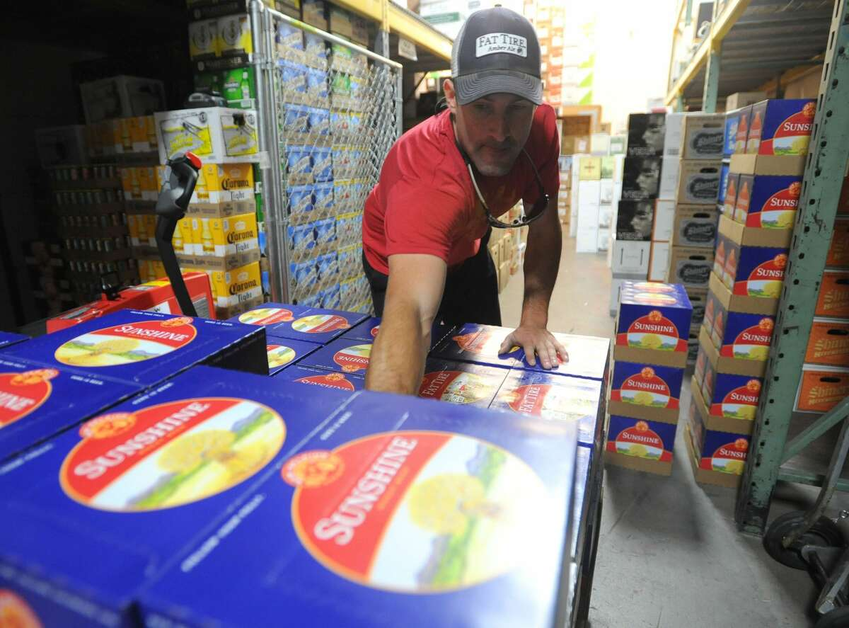 Greg Kus, a delivery person for New Belgium Brewery, removes 12-packs from a palette as he delivers beer to Wilbur's Beverage in Fort Collins, Colo., in this file photo.