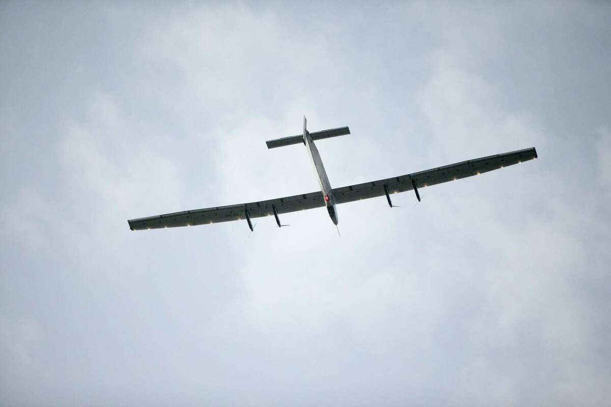 The Solar Impulse 2, a solar-powered airplane, circles the Kalaeloa Airport, Friday, July 3, 2015, in Kapolei, HI. The plane, piloted by Andre Borschberg, is attempting to fly around the world without fuel. (AP Photo/Marco Garcia)