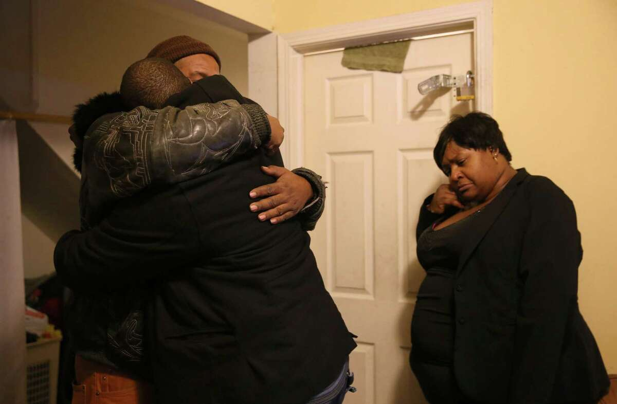 Melvin Jones, facing camera, hugs Robin Andrews, both brothers of Bettie Jones, 55, in Jones' living room after she was shot and killed by a Chicago police officer in Chicago on Saturday.