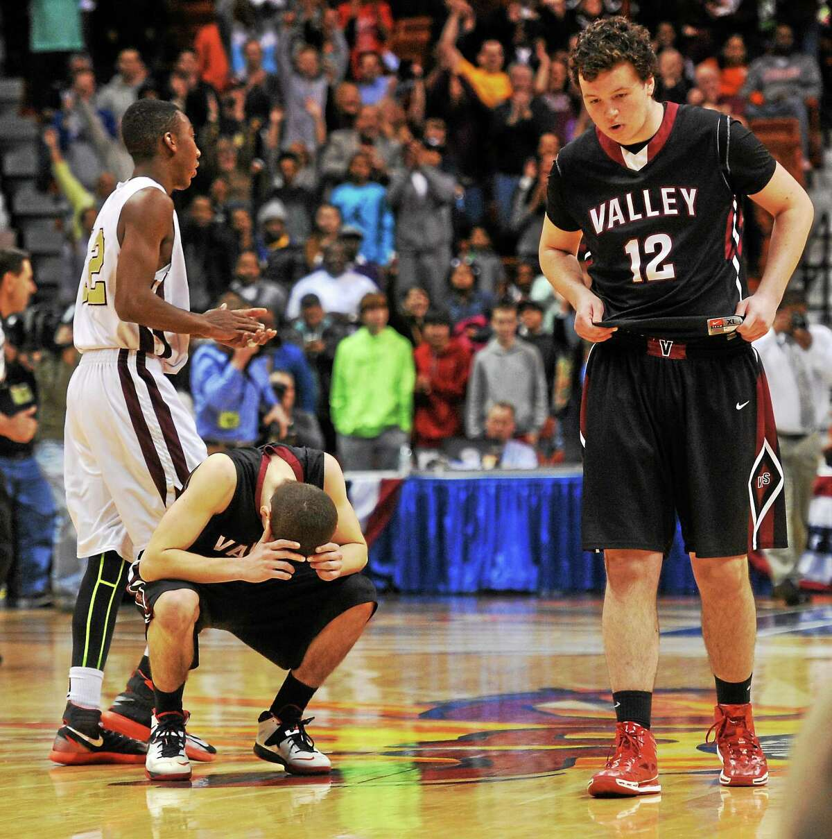 David Bradbury Jr., Brennan Joy (12) and Valley Regional battled Charles Fisher, left, and Sacred Heart to the end on Sunday, but came up short and lost 65-56 in the Class S state championship game.