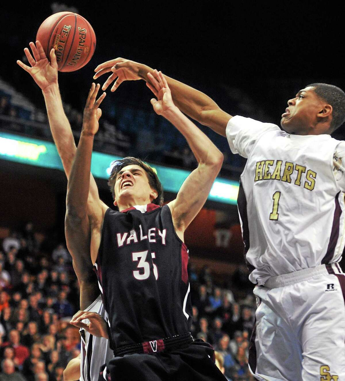 Sacred Heart's Malik Petteway, right, and Mustapha Heron, defend Valley Regional's Hunter Linfesty during Sunday's Class S state title game.
